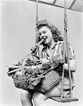 1940s WOMAN SITTING ON A ROPE SWING WITH A WICKER BASKET OF FRESH VEGETABLES ON HER LAP WHILE EATING A CARROT