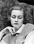 1930s PORTRAIT OF WOMAN LOOKING DOWN WITH SAD EXPRESSION AND HER CHIN RESTING ON INDEX FINGER