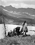 1920s 1930s TWO WOMEN ONE MAN RIDING HORSES WESTERN SADDLES COWBOY WEARING WOOL CHAPS BY MOUNTAIN LAKE IN CANADA