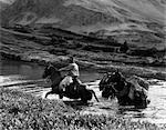 COWBOY WEARING ANGORA CHAPS CROSSING A STREAM LEADING TWO PACK HORSES LOADED WITH EQUIPMENT BAKER LAKE ALBERTA CANADA
