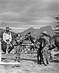 1930s TWO COWBOYS & A WOMAN GROOMING A HORSE NEAR THE CORRAL THE STANDING COWBOY IS WEARING BATWING CHAPS