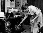 1950s HOUSEWIFE TESTING ROAST BEEF IN OVEN TO SEE IF IT IS DONE COOKING