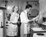 1950s SMILING HAPPY COUPLE MAN AND WOMAN HUSBAND AND WIFE WASHING DRYING DISHES TOGETHER IN KITCHEN