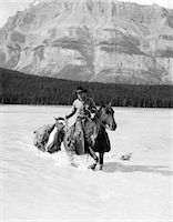 1930s COWBOY WITH BATWING CHAPS ON A BAY HORSE CROSSING A RIVER LEADING A PAINT PACK HORSE WITH MOUNTAINS IN BACKGROUND    Stock Photo - Premium Rights-Managednull, Code: 846-02793220