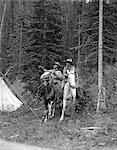 1920s TWO MEN RIDING HORSES THROUGH CAMP GROUNDS IN FOREST COWBOY HAT TENT ADVENTURE COWBOYS BOTH ARE WEARING ANGORA CHAPS