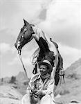 1930s COWBOY SITTING IN FRONT OF HORSE HOLDING REINS SPOTTED PAINT PINTO