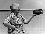 1930s 1940s GRANDMOTHER IN APRON ADMIRING LOAF OF FRESHLY BAKED BREAD