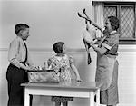 1940s HOUSEWIFE SHOWING RAW FRESH PLUCKED TURKEY TO SON AND DAUGHTER IN KITCHEN
