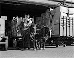 TURN OF THE CENTURY AFRICAN AMERICAN MAN PULLING WAGON DRAWN BY TWO HORSES OUT OF TRUCK TERMINAL