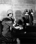1920s SMILING WOMAN WITH PEN TO LIPS WRITING A LETTER AT DESK WITH LAMP IN HOTEL LOBBY WEARING CLOCHE HAT AND FUR COLLAR COAT