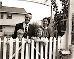 1950s FAMILY OF FOUR BEHIND PICKET FENCE IN BACKYARD SMILING AT CAMERA