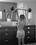 1950s BOY EXERCISING WITH DUMBBELL AT MIRROR IN BEDROOM    Stock Photo - Premium Rights-Managed, Artist: ClassicStock, Code: 846-02793549