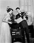 1950s TEEN COUPLE BOY AND GIRL IN PROM FORMAL WEAR PLAYING PHONOGRAPH RECORDS IN HOME LIVING ROOM