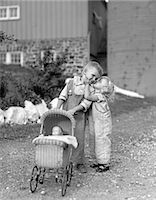 people kissing little boys - 1930s 1940s LITTLE GIRL KISSING BOY PUSHING TOY BABY CARRIAGE IN FRONT OF BARN    Stock Photo - Premium Rights-Managednull, Code: 846-02793643