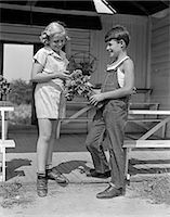 1940s BOY WEARING OVERALLS GIVING GIRL BOUQUET FLOWERS AT FARM STAND    Stock Photo - Premium Rights-Managednull, Code: 846-02793664