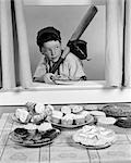 1950s BOY IN BASEBALL GARB WITH BAT SNEAKING PIE THROUGH OPEN WINDOW