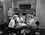 1950s GIRLS PLAYING SCRABBLE IN REC ROOM WITH BOY CHANGING RECORDS