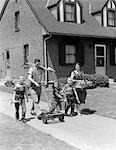 1950s FAMILY OF FIVE ON SUBURBAN SIDEWALK WALKING WITH GARDENING TOOLS LAWNMOWER & FLOWERS