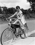 1940s BOY ON AN ELGIN BIKE CARRYING NEWSPAPERS IN A SLING WEARING KNEE SOCKS AND SNEAKERS