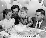 1950s CLOSE-UP OF FAMILY OF 4 WITH SON BLOWING OUT 2 CANDLES ON HIS BIRTHDAY CAKE