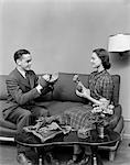 1940s COURTING TEENAGE COUPLE SITTING ON COUCH UNWINDING A SKEIN OF KNITTING YARN WOOL    Stock Photo - Premium Rights-Managed, Artist: ClassicStock, Code: 846-02793779