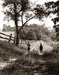 1930s REAR VIEW OF BOY & GIRL IN STRAW HATS & OVERALLS WALKING DOWN FARM ROAD WITH DOG BETWEEN THEM