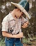 BOY WEARING STRAW HAT REMOVING HOOK FROM MOUTH OF FISH OUTDOOR