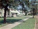 1950s SUBURBAN STREET WHITE HOUSES WITH SIDEWALK RUNNING DOWN MIDDLE OF IMAGE YARD GREEN GRASS SPRING LAKE NJ