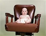 1960s CHUBBY BALD BABY WEARING CLOTH DIAPER SITTING IN EXECUTIVE OFFICE BUSINESS CHAIR