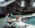 1950s FAMILY OF 4 BACKYARD SWIMMING POOL HOUSE MOM SERVING FOOD MEAL AT TABLE BY GRILL DAD BOY GIRL SUMMER LAWN FURNITURE