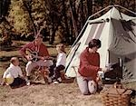 PARENTS WITH SON AND DAUGHTER OUTSIDE TENT PLAYING GUITAR AND COOKING ON GRILL FOUR MAN WOMAN BOY GIRL VACATION 1960s