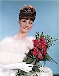 1960s YOUNG TEENAGE WOMAN IN FORMAL DRESS HOLDING BOUQUET ROSES BEE HIVE HAIRDO TIARA PROM BEAUTY QUEEN FASHION