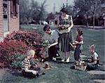 1950s SUBURBAN FAMILY GARDENING TOGETHER IN THE SPRINGTIME