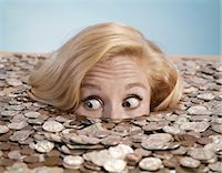 1960s STARTLED BUG-EYED BLOND YOUNG WOMAN BURIED UP TO HER NOSE IN PILE OF COINS AND CURRENCY    Stock Photo - Premium Rights-Managednull, Code: 846-02794267
