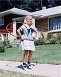 1950s 1960s YOUNG BLOND GIRL PLAYING WITH HULA HOOP OUTSIDE ON SUBURBAN SIDEWALK IN SAILOR STYLE DRESS
