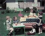 1950s AMERICANA GIRLS AND BOYS IN BUSINESS WITH A LEMONADE AND SNACK FOOD STAND ON THE 4TH OF JULY