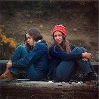 sad girls - 1970s TWO SAD SERIOUS TEENAGE GIRLS SITTING BACK TO BACK OUTSIDE    Stock Photo - Premium Rights-Managednull, Code: 846-02794558