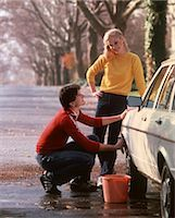 1970 1970s YOUNG COUPLE TEENS BOY GIRL MAN WOMAN WASHING CAR WASH AUTO 1980 1980s    Stock Photo - Premium Rights-Managednull, Code: 846-02794837