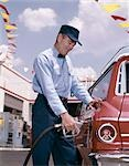 1950s 1960s SERVICE STATION ATTENDANT WITH GASOLINE PUMP HOSE FILLING GAS TANK OF AUTOMOBILE