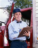 1950s 1960s MAN DRIVER DELIVERY SERVICE REPAIRMAN IN UNIFORM CAP BOW TIE HOLDING CLIPBOARD STANDING IN OPEN DOOR OF TRUCK CAB    Stock Photo - Premium Rights-Managednull, Code: 846-02794844