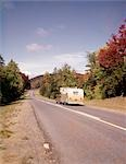 1960s CAR PULLING RV CAMPER DOWN COUNTRY ROAD ADIRONDACKS NEW YORK AUTUMN