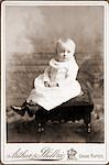 FORMAL STUDIO PORTRAIT OF BABY IN HIGH BUTTONED SHOES AND LONG DRESS
