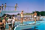1970s CROWD OF TEENS IN POOL & ON DIVING BOARD AT MUNICIPAL SWIM POOL MCPHERSON KANSAS SUMMER FUN RECREATION COOL WET