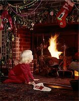 1960s SMALL BLOND GIRL AT FIREPLACE DECORATED FOR CHRISTMAS HOLDING STOCKING LOOKING FOR SANTA CLAUS    Stock Photo - Premium Rights-Managednull, Code: 846-02795254
