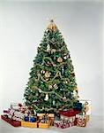 1950s 1960s 1970'S COLORFUL DECORATED CHRISTMAS TREE SURROUNDED BY PRESENTS STUDIO INDOOR