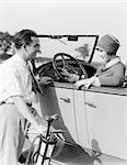 1920s 1930s MAN IN SHIRT AND TIE HOLDING GOLF BAG STANDING NEXT TO WOMAN SITTING IN A CONVERTIBLE SEDAN HAND ON STEERING WHEEL