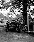 1920s COUPLE MAN WOMAN ENTER MOTOR CAR CARRYING BAGS FASHION TRIP LEISURE GETAWAY GOLF BAGS UPSCALE CONVERTIBLE