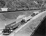 1950s LINE OF TRAFFIC WITH MANY TRUCKS & CARS & FREIGHT TRAIN PASSING ON ADJACENT HILLSIDE