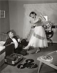 1950s 1960s TEEN COUPLE IN LIVING ROOM IN PROM DRESS & TUXEDO GUY SITTING ON FLOOR & GIRL DANCING TO MUSIC FROM A RECORD PLAYER