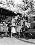 1920s COUPLE WOMEN MAN AT ROADSIDE PRODUCE STAND BUYING PUMPKINS